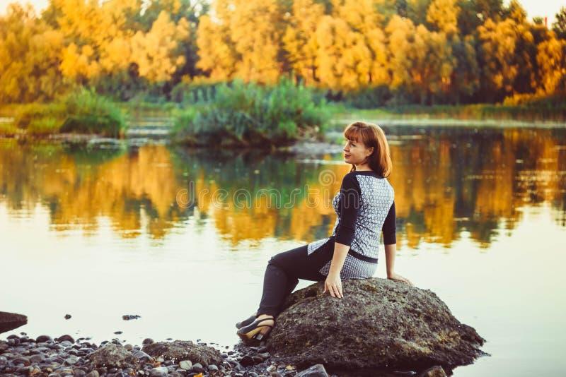Kvinnan på stenen vid floden royaltyfria foton
