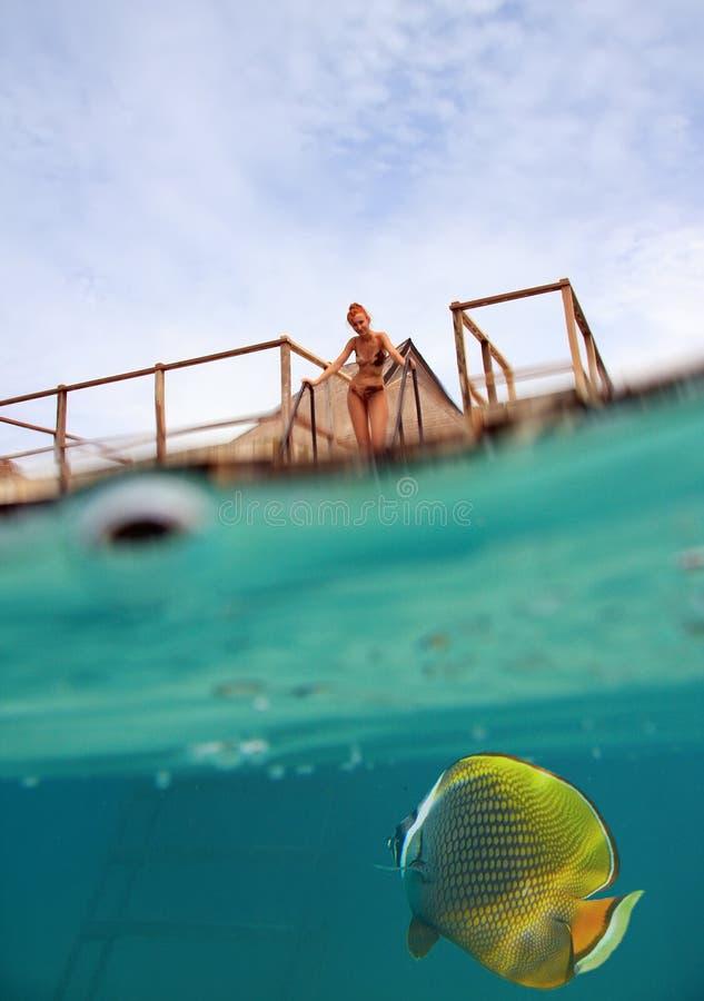 Kvinnan på trappan på nedstigningen till havet och a under vattensikten, person är synliga till och med vattendroppar arkivfoto