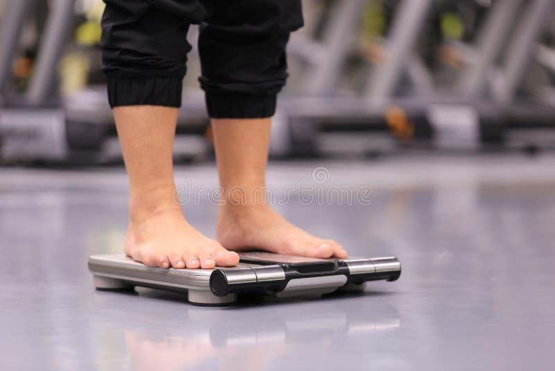 Kvinnan på viktskalan för kontrollvikt i idrottshallen, bantar och royaltyfri foto