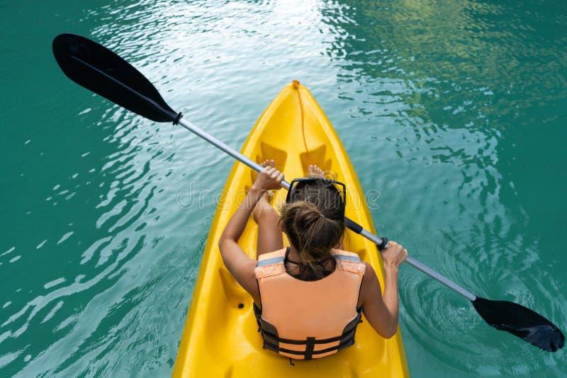 Kvinnan paddlar kajaken i sjön med turkosvatten royaltyfri foto