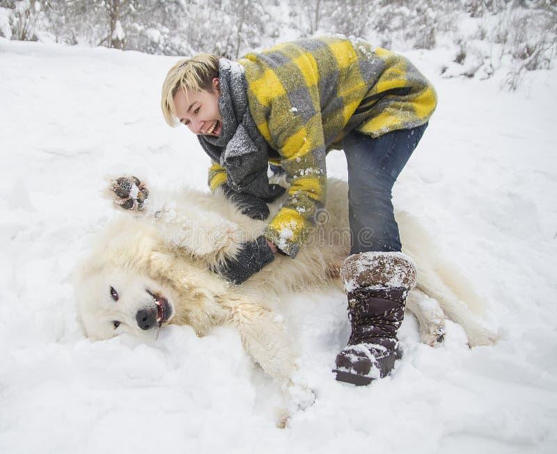 Kvinnan plaskar med en vit hund i snö arkivbilder