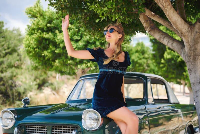 Kvinnan poserar nära den retro bilen arkivbild