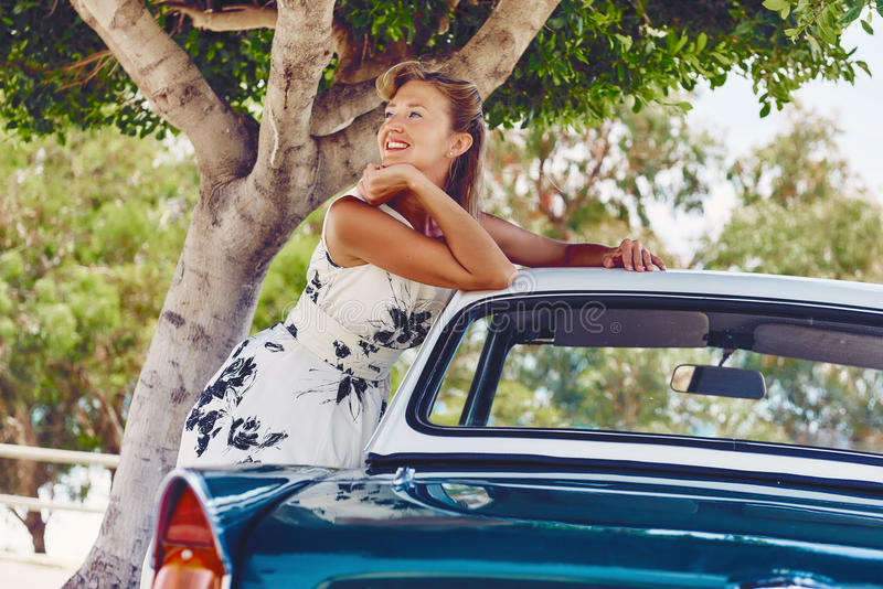 Kvinnan poserar nära den retro bilen royaltyfri foto