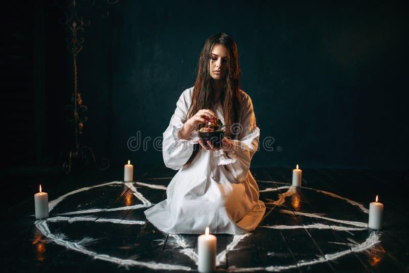 Kvinnan producerar en ritual av svart magi, ockultism royaltyfri fotografi