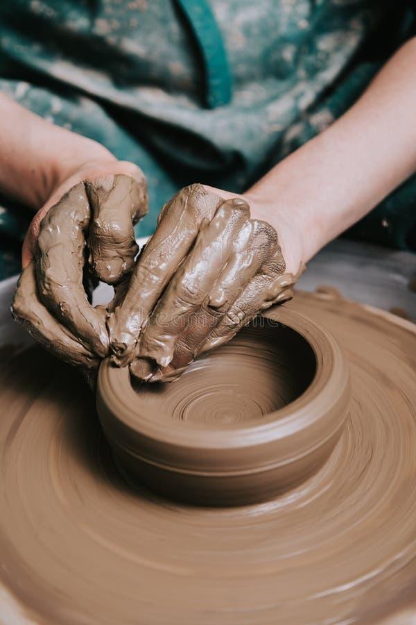 Kvinnan räcker arbete på krukmakerihjulet royaltyfri foto