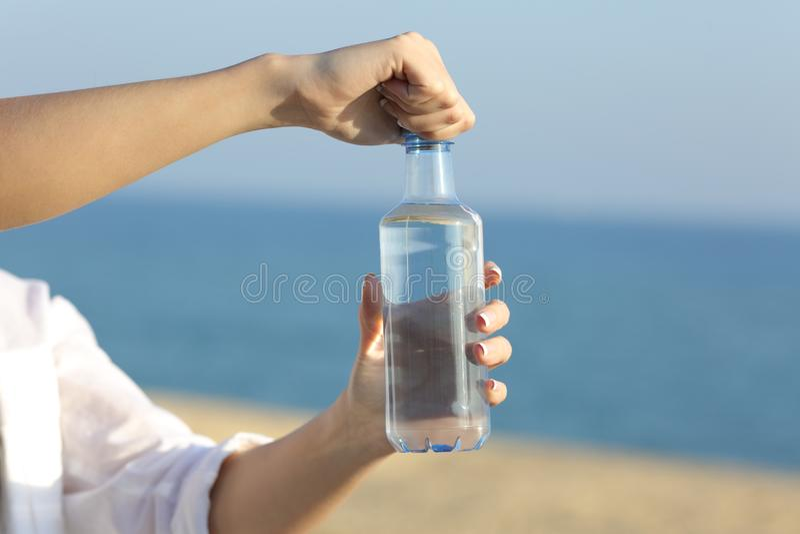 Kvinnan räcker att öppna en flaska av vatten utomhus royaltyfri bild