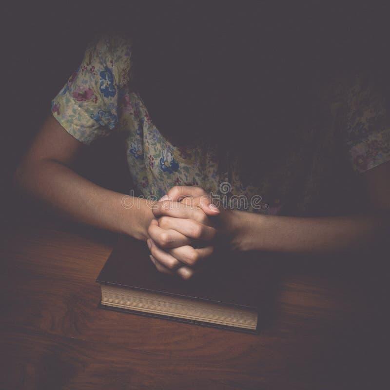 Kvinnan räcker att be med en bibel, tappningsignal royaltyfria foton