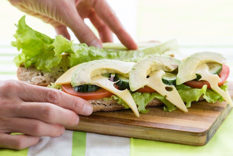 Kvinnan räcker att förbereda den sunda frukosten som gör den läckra smörgåsen royaltyfri fotografi