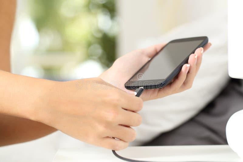 Kvinnan räcker att plugga en uppladdare i en smart telefon arkivfoton