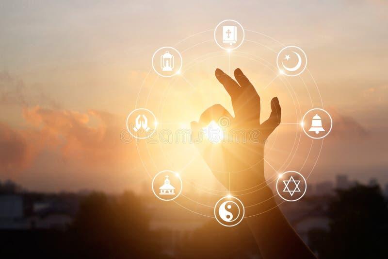 Kvinnan räcker be och religionsymbolen på solnedgångbakgrund arkivbilder