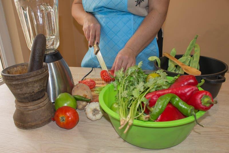 Kvinnan räcker bitande grönsaker på köksvart tavla sund mat Kvinna som förbereder grönsaker som lagar mat sunt mål i kitchen arkivbild