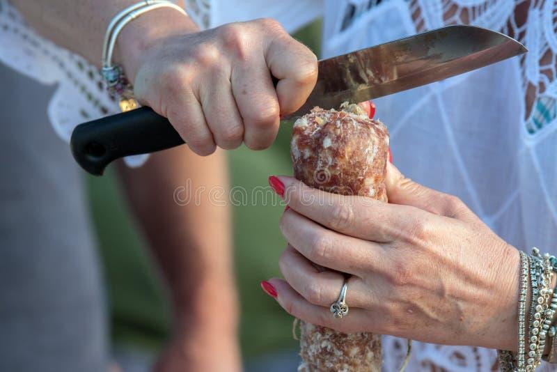Kvinnan räcker bitande salami arkivbilder