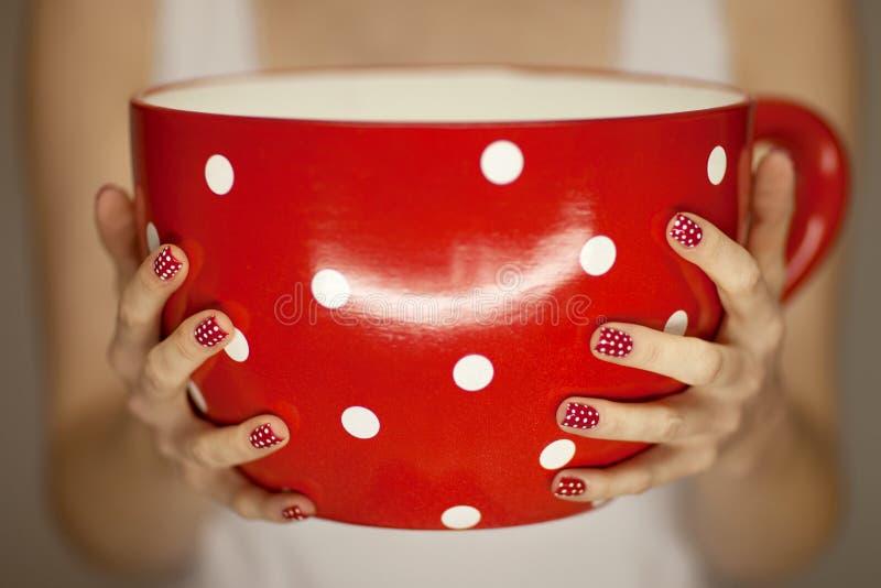 Kvinnan räcker den hållande jätte- kaffekoppen arkivbilder
