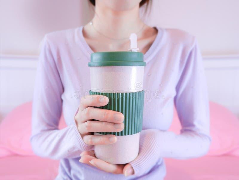 Kvinnan räcker den hållande kaffekoppen Flickan, i att rymma för tröja, rånar Morgondrinklivsstil royaltyfri bild