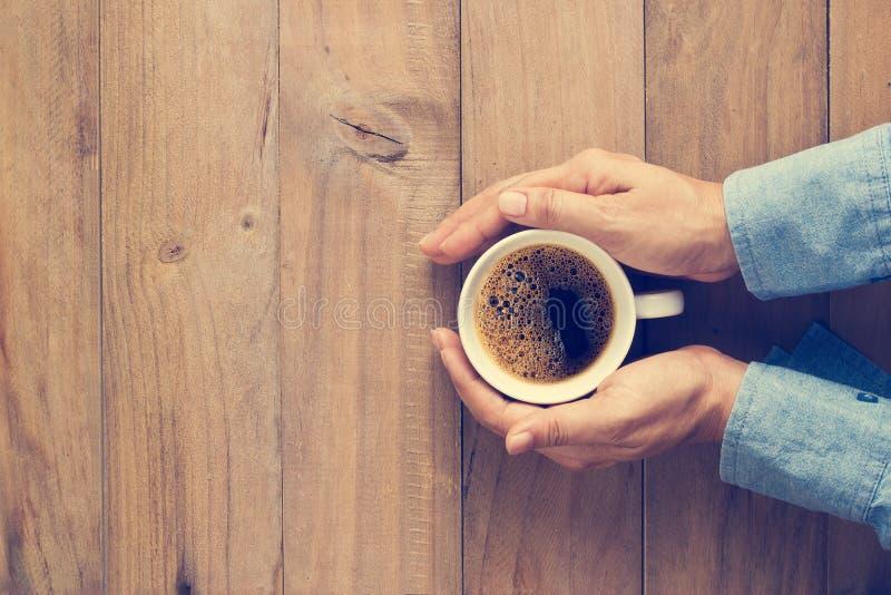 Kvinnan räcker den hållande koppen kaffe på träbakgrund royaltyfri foto