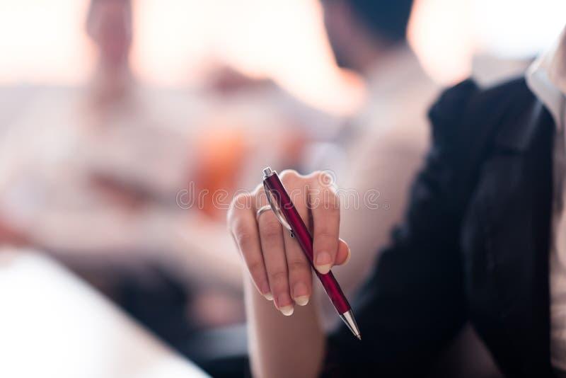 Kvinnan räcker den hållande pennan på affärsmöte royaltyfri bild