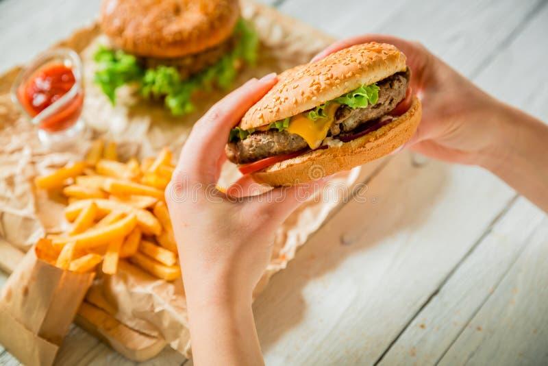 Kvinnan räcker den hållande smakliga amerikanska hamburgaren, och fransmannen steker, sås på träplattan royaltyfri foto
