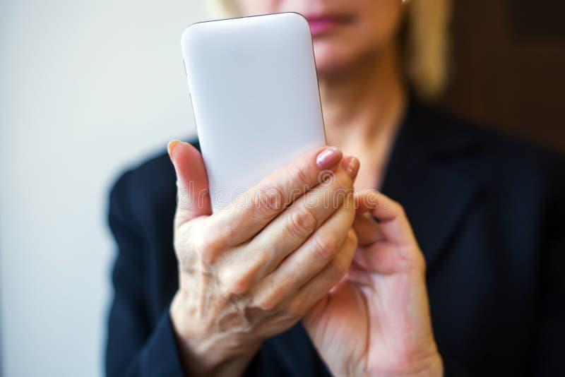 Kvinnan räcker den hållande vita mobiltelefonen closeup arkivfoton