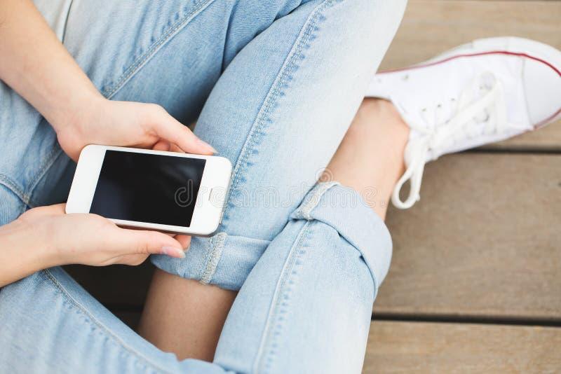 Kvinnan räcker den rörande smartphonen royaltyfri bild