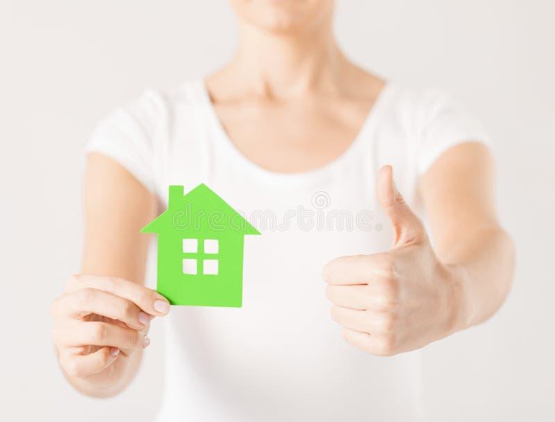 Kvinnan räcker det hållande gröna huset