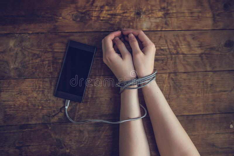 Kvinnan räcker fångat och slåget in på handleder med mobiltelefonkabel som handbojor i smart telefonnätverkande- och kommunikatio fotografering för bildbyråer