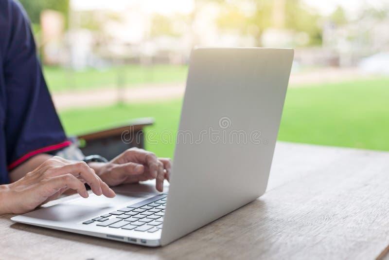 Kvinnan räcker genom att använda bärbara datorer och har en anteckningsbok och en penna med varmt ljus royaltyfri fotografi