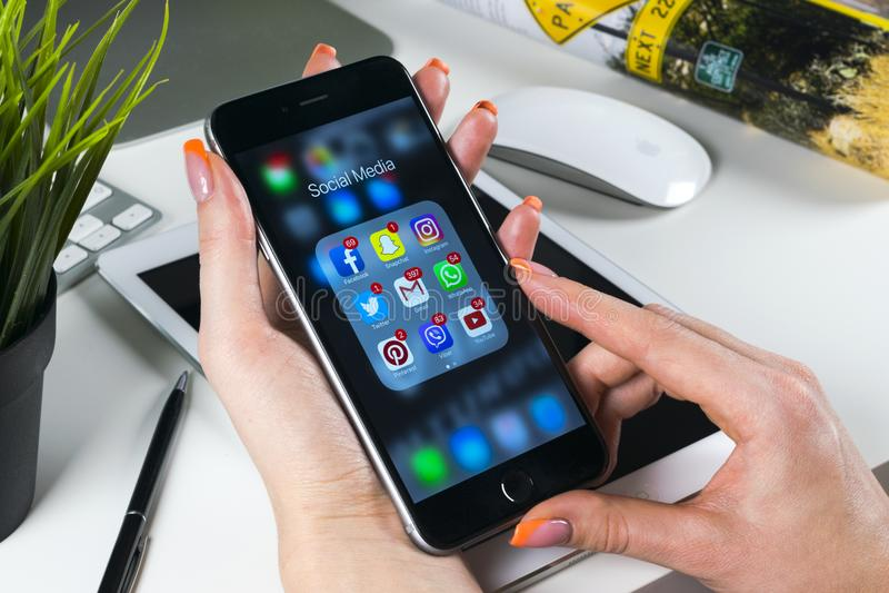 Kvinnan räcker genom att använda iphone 7 med symboler av social massmediafacebook, instagram, kvittrandet, den Google applikatio arkivbild
