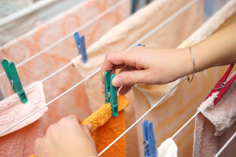 Kvinnan räcker hängande kläder för att torka på kläder-linje efter tvätteri royaltyfri bild