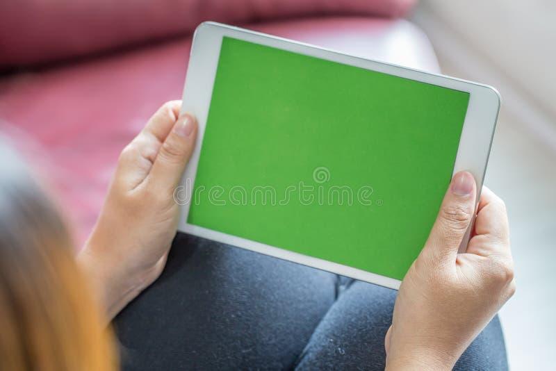 Kvinnan räcker hållande minnestavlaPC med den gröna skärmen arkivfoto