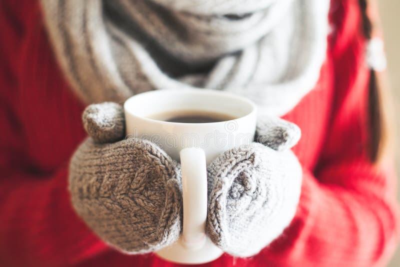 Kvinnan räcker i krickahandskar som rymmer en råna med varmt kaffe royaltyfri foto