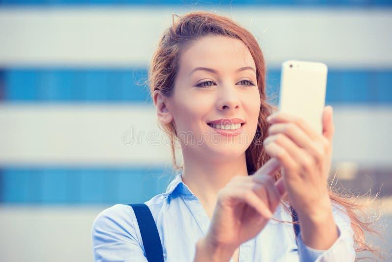 Kvinnan räcker innehavet, att använda som är smart, mobiltelefon royaltyfri foto