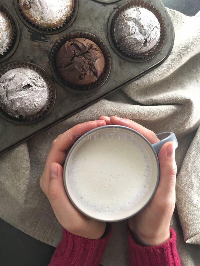 Kvinnan räcker innehavet som koppen av mjölkar nära skrivbordet med muffin fotografering för bildbyråer