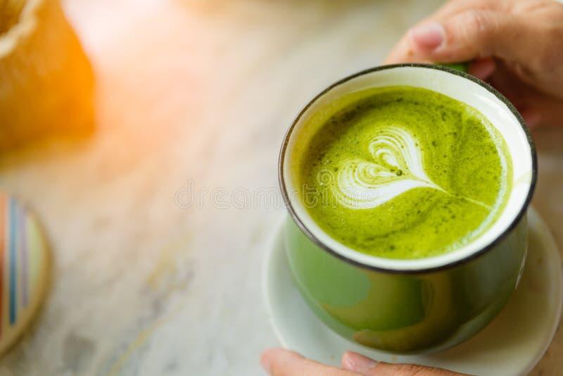 Kvinnan räcker innehavkoppen av varmt grönt te med formad hjärta arkivfoton