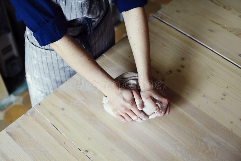 Kvinnan räcker närbilden som bildar rå lera i en studio för seminarium för keramiker` s Hantverk-arbete fotografering för bildbyråer