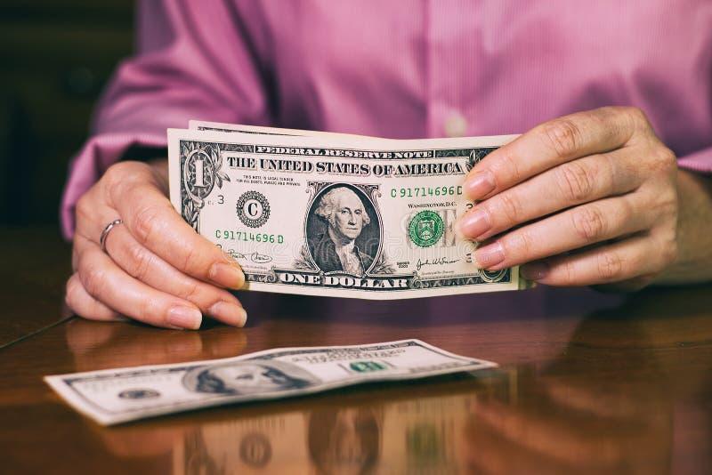 Kvinnan räknar dollarräkningar royaltyfria bilder