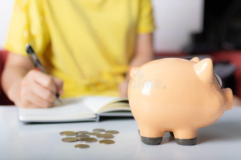 Kvinnan räknar myntet i piggybank arkivfoto