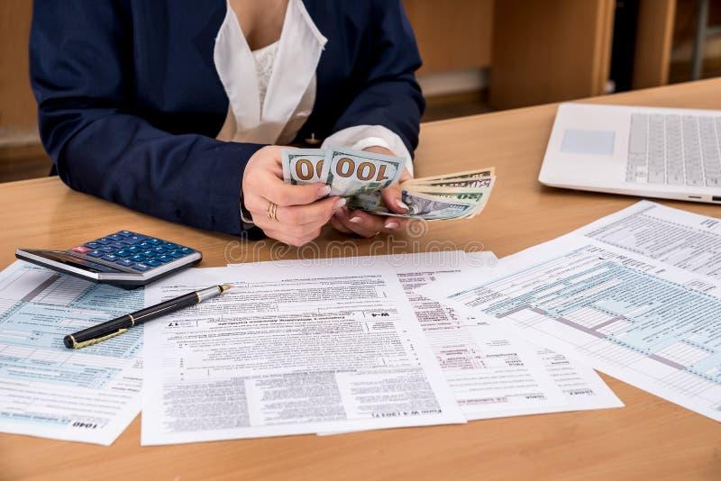 Kvinnan räknar pengar, genom att fylla i skatt royaltyfri foto