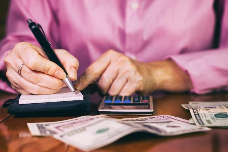 Kvinnan räknar pengarna och skriver resultatet till anmärkningen arkivbild
