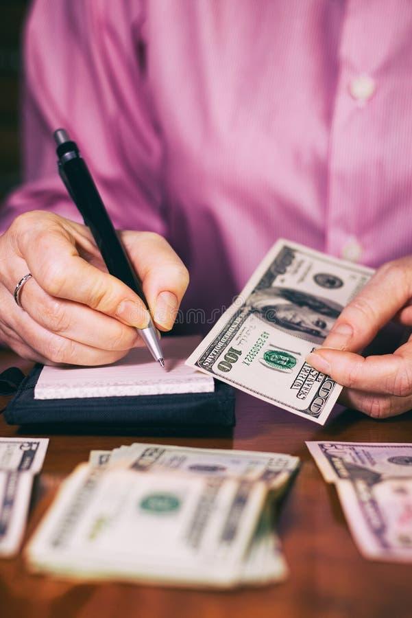 Kvinnan räknar pengarna och skriver resultatet till anmärkningen arkivfoton
