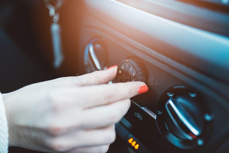 Kvinnan reglerar ventilation i hennes bil royaltyfri fotografi