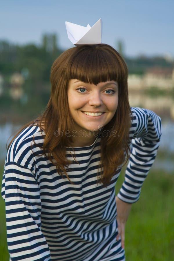 Kvinnan rev in av t-kort med det pappers- skeppet på hennes huvud arkivfoton