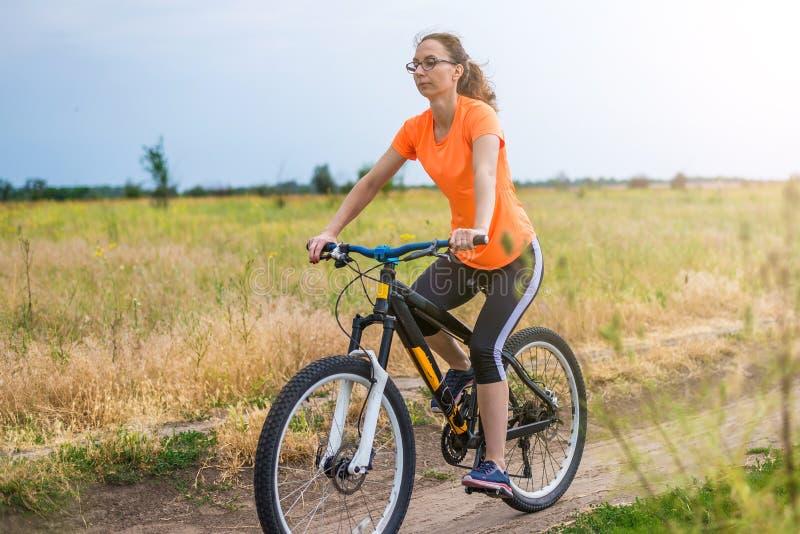 Kvinnan rider en cykel, en aktiv livsstil arkivbilder