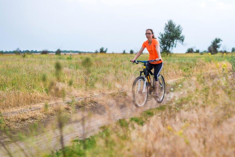 Kvinnan rider en cykel, en aktiv livsstil royaltyfria bilder