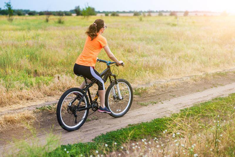 Kvinnan rider en cykel, en aktiv livsstil arkivfoto