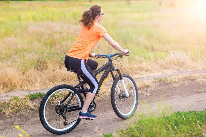 Kvinnan rider en cykel, en aktiv livsstil arkivbild