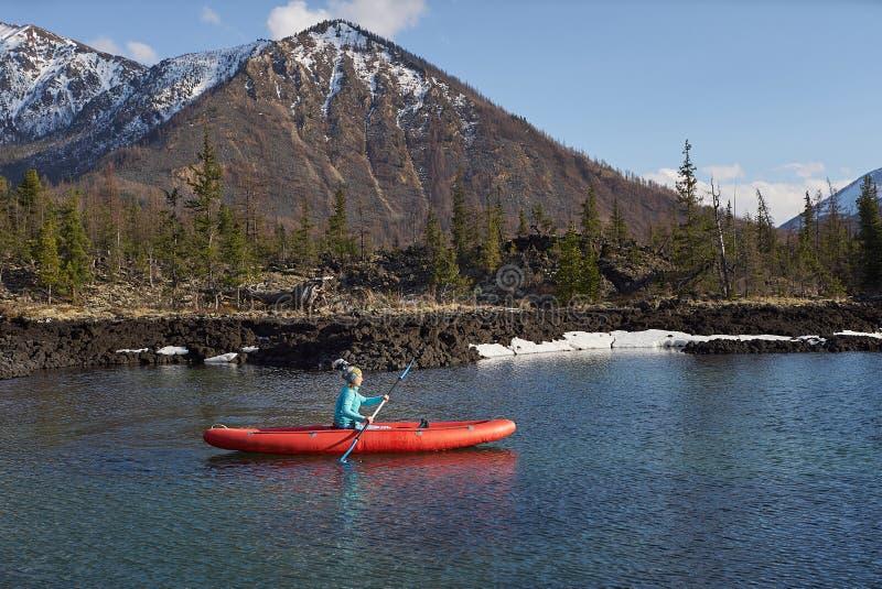 Kvinnan rider kanoten på sjön i bergområde i vårtid royaltyfri foto