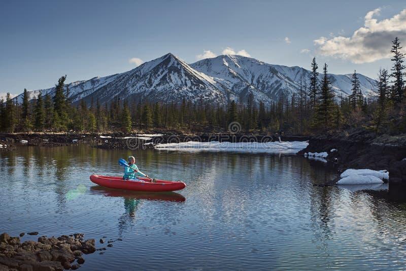 Kvinnan rider kanoten på sjön i bergområde i vårtid royaltyfri fotografi