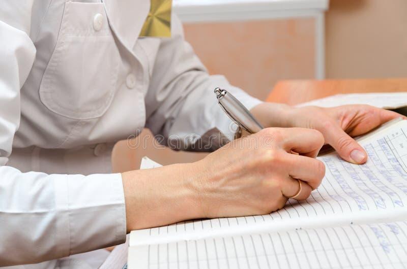 Kvinnan-roentgenographer i poliklinikkontor skriver tålmodiga data royaltyfri foto