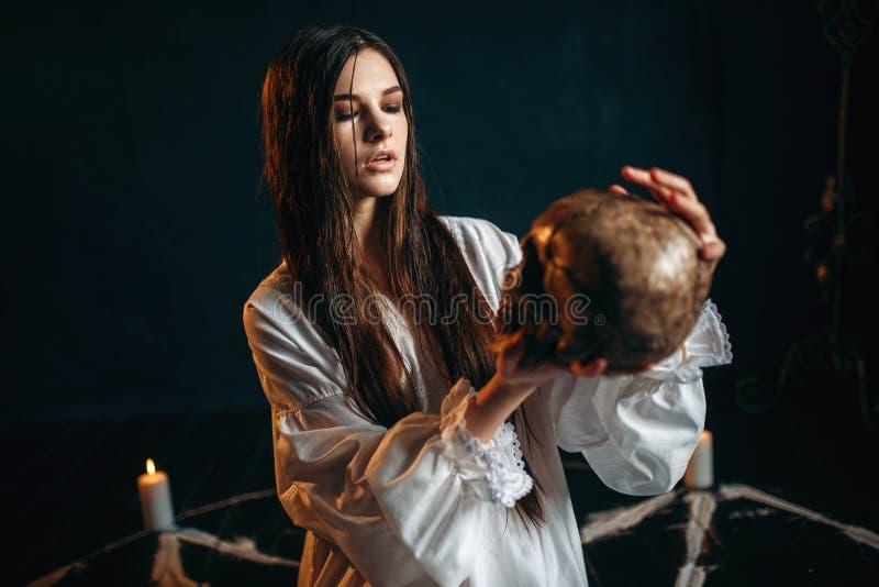 Kvinnan rymmer den mänskliga skallen i handen, mörk magi, häxa arkivbild