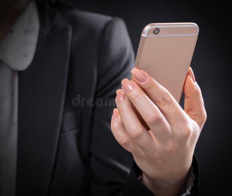 Kvinnan rymmer den nya mobiltelefonen arkivfoto